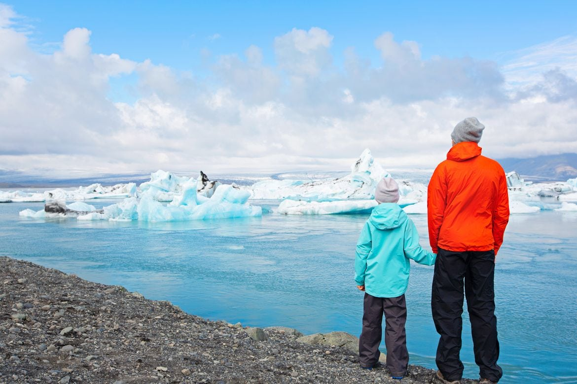 why you need to take and Iceland family vacation - father and child looking at icebergs in jokulsarlon lagoon in Iceland