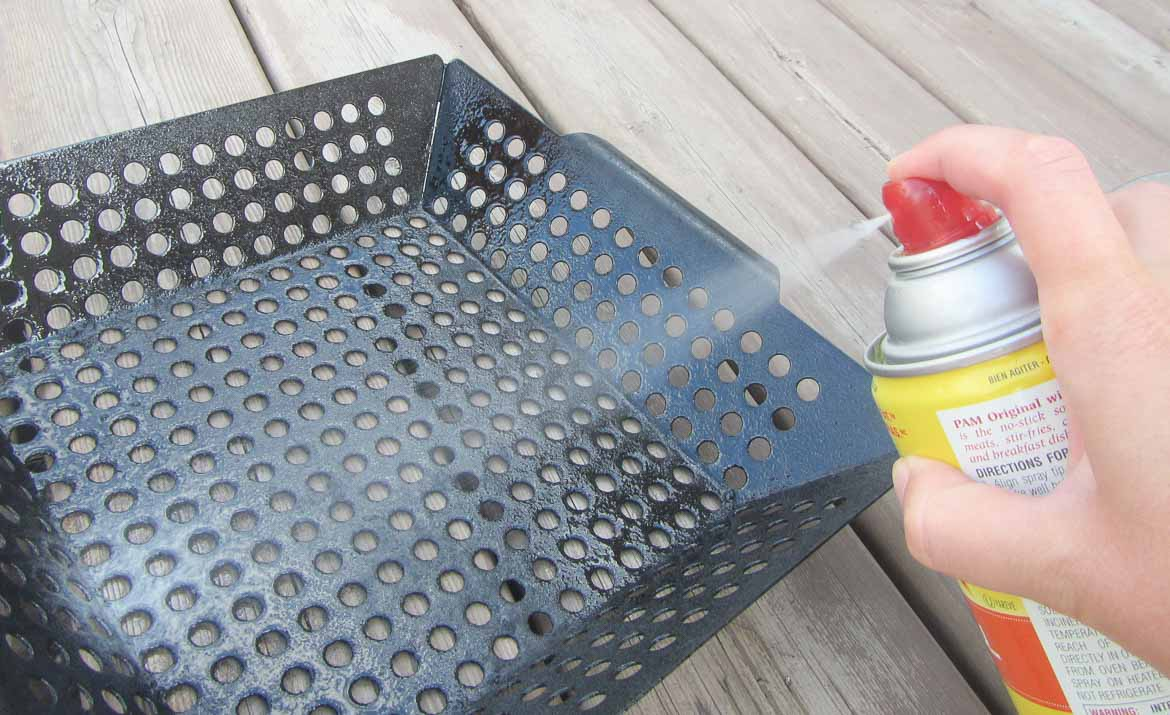 spraying grill basket with cooking oil