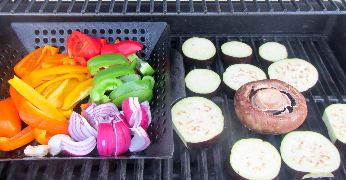 veggies grilling in a basket with portabella mushroom and eggplant slices on the side