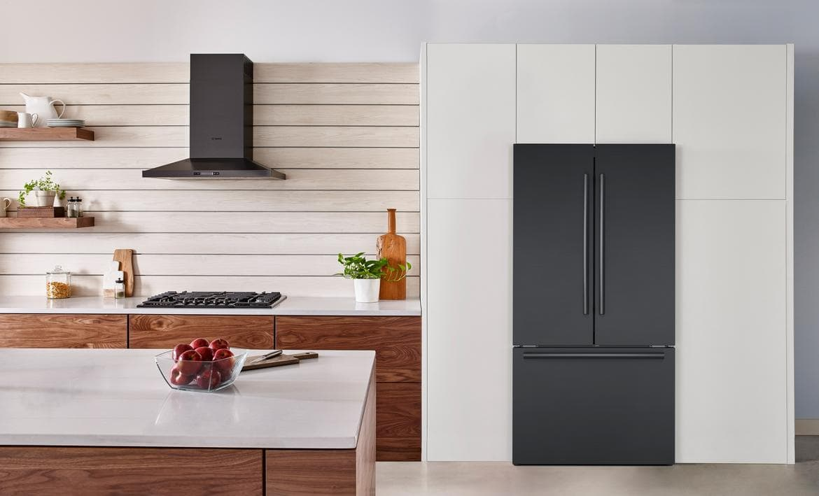 Bosch counter-depth refrigerator with double doors and a single freezer compartment in white kitchen