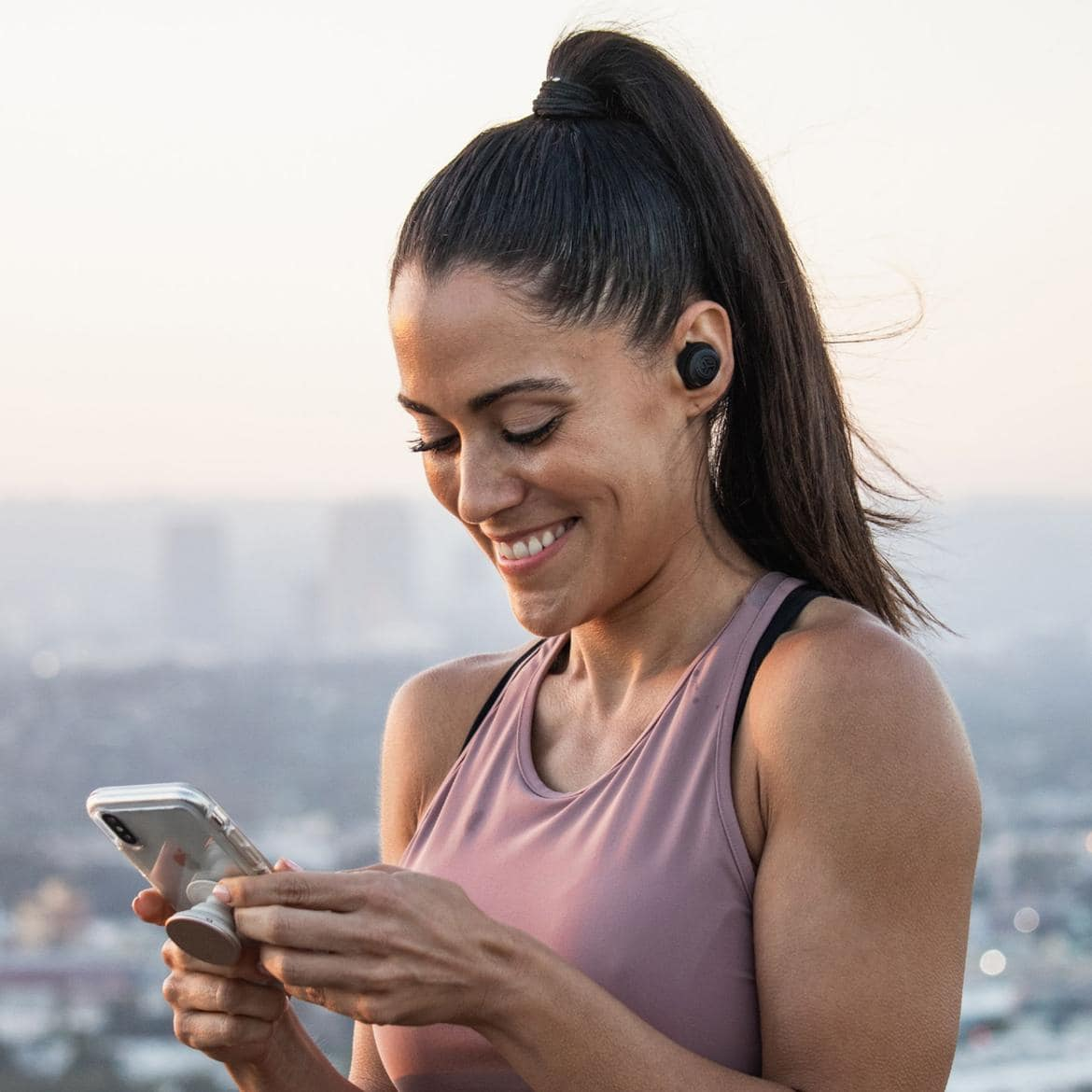 JLab true wireless earbuds under $100 worn by woman holding smartphone