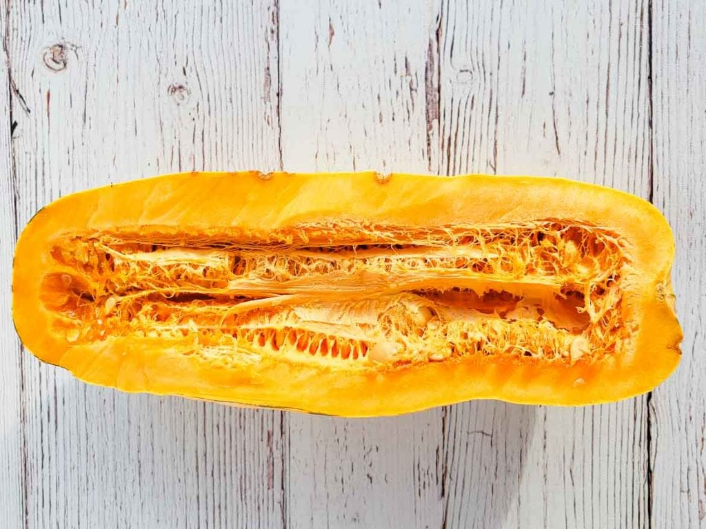 inside of a delicata squash cut in half with seeds and membranes