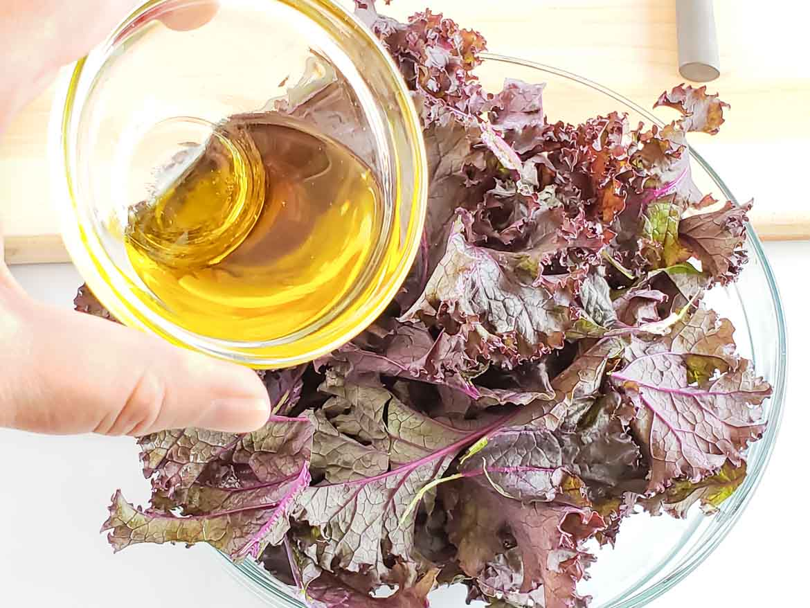 adding olive oil to purple kale chips