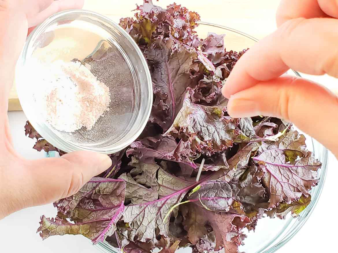 sprinkling purple kale chips with salt before baking