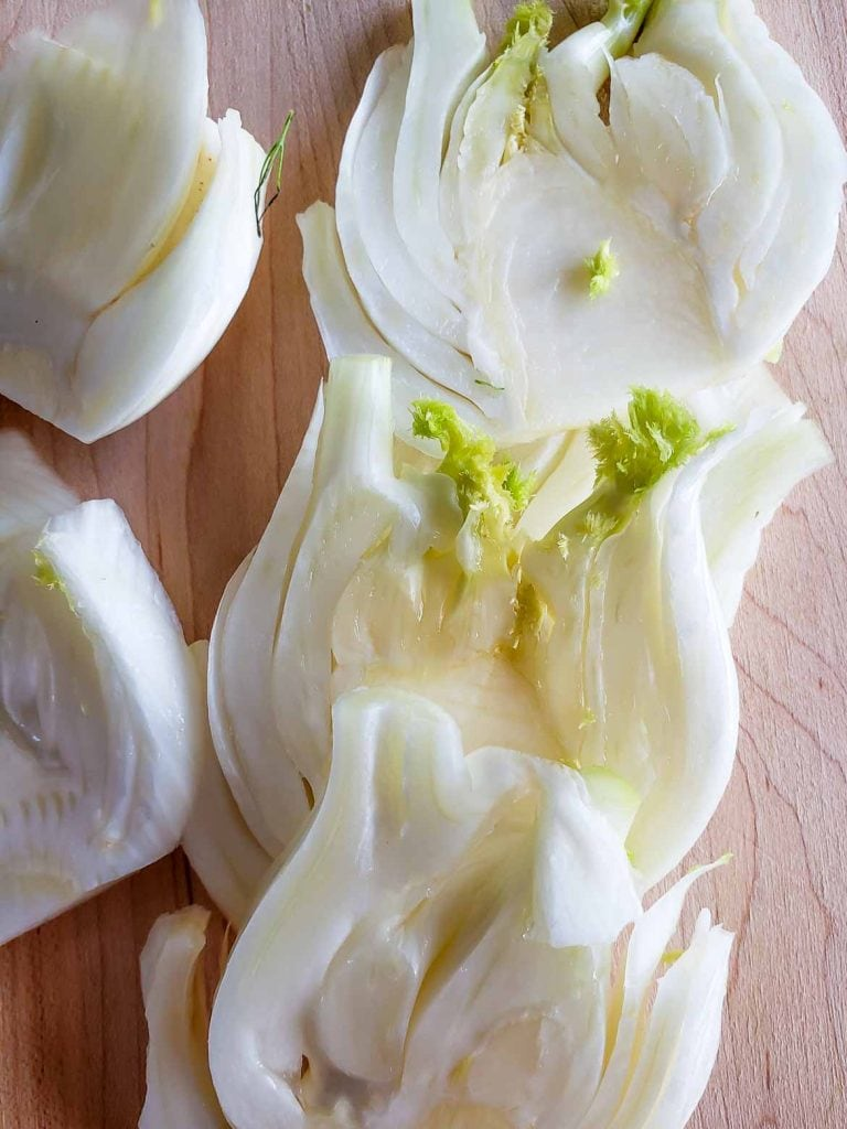 fennel cut into slices on a wooden cutting board