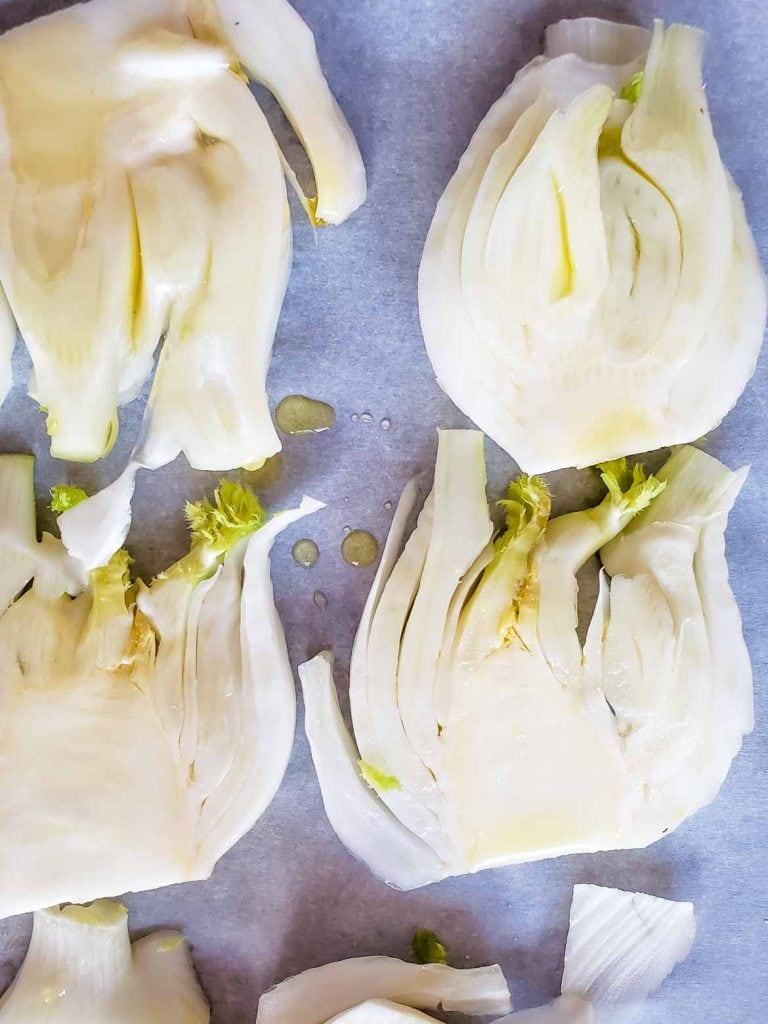 fennel bulb slices on a pan drizzled with olive oil