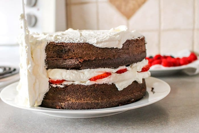 half iced cake with whipped cream frosting on chocolate cake with fresh berries