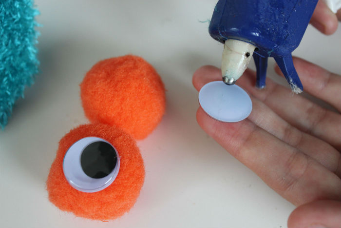 Adorable DIY Sock Monster Puppet Gluing Eyes