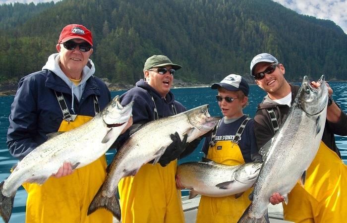 3 generations of men holding big salmon