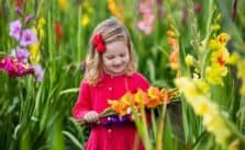 Growing An Edible Flower Garden For Kids child holding gladiolus flowers